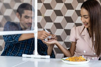 Asian couple cleaning hand befor meal, New normal eating out.
