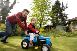 A man pushing a young boy on a toy tractor