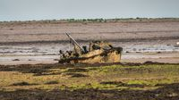 A damaged boat in the mud, seen near Barrow-In-Furness, Cumbria, England