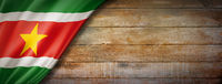 Suriname flag on vintage wood wall banner