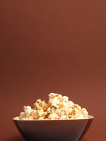 Fresh popcorn on a brown background with space for text