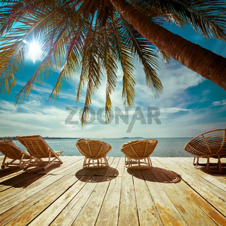 Tropical beach with palm tree and chairs for relaxation on wooden terrace