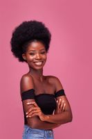 Beautiful African American girl with gorgeous afro hairstyle standing smiling with arms folded in black top and denim jeans isolated on pink background