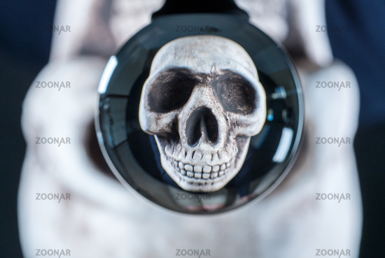 Human skull reflected in a glass ball with the original skull behind for Halloween
