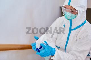Putzkraft in Schutzkleidung studiert Desinfektionsmittel in Klinik