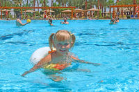 smiling baby girl with nice plaits swimming in swimming pool lying on inflatable circle on summer ho