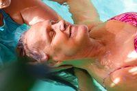 Smiling woman receiving water spa in pool