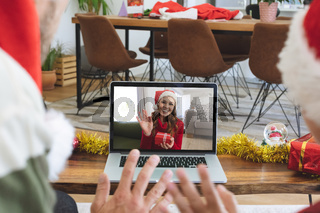 Rear view of man and son in santa hats waving while having a videocall with woman in santa hat wavin