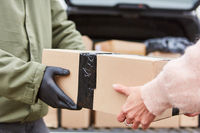 Persönliche Übergabe von Paket durch Lieferant