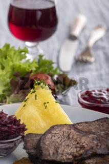 deutscher Sauerbraten auf einem Teller mit Knödeln