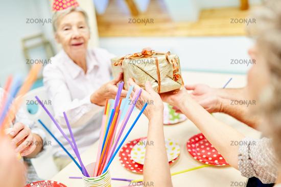 Seniorin feiert Geburtstag und bekommt Geschenk