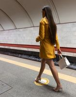 Rear view of a walking on subway platform beautiful young girl with long beautiful legs wearing a yellow spring coat and a white handbag or purse in hand