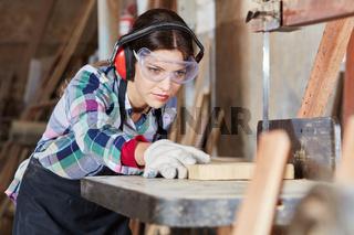 Frau beim Holz sägen in Schreinerei