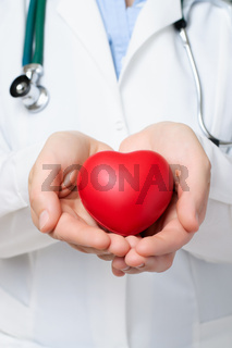 Female doctor protecting a red heart with her hands