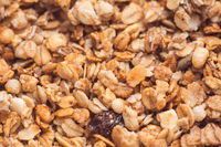 Useful and tasty muesli with nuts, rasins and flakes. Selective focus macro shot with very shallow depth of field. Healthy and vegetarian lifestyle