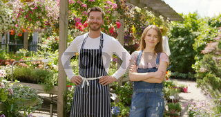 Outdoors shot of cheerful male and female gardeners looking at camera