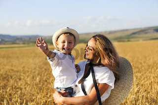 Mother holding son on hands and walking in field
