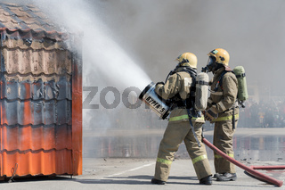 Two firefighters extinguishes fire from fire hose, using firefighting water-foam barrel with air-mechanical foam
