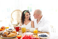 Loving tender pregnant couple at table with breakfast