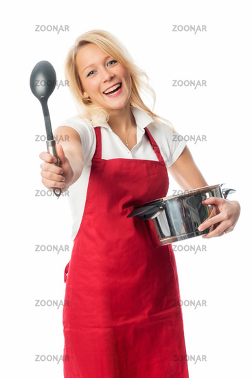 woman with apron holding a soup spoon up
