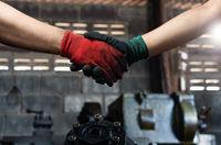 Male and female industrial workers shaking hands in factory workshop wearing protective workwear - Business and commercial teamwork within the workplace - Working together, goals and success concept