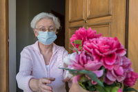 Senior woman with face mask gets flowers at the house door