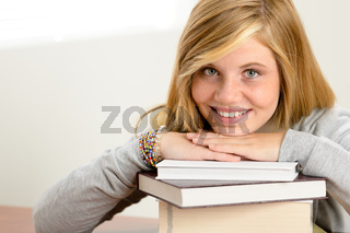 Smiling student teenager leaning head on books