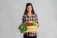 Young brunette holding a box full of fresh fruit and vegetable