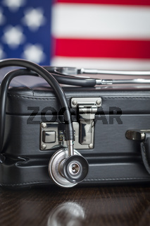 Briefcase and Stethoscope Resting on Table with American Flag Behind