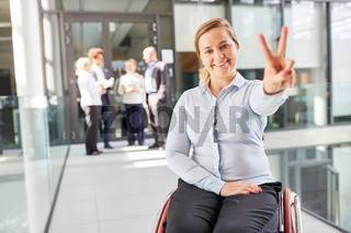 Junge Geschäftsfrau im Rollstuhl macht Handzeichen