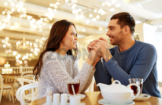 happy couple with tea holding hands at restaurant