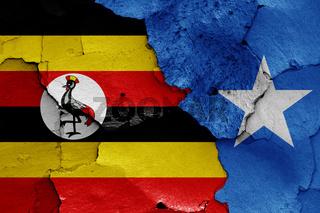 flags of Uganda and Somalia painted on cracked wall