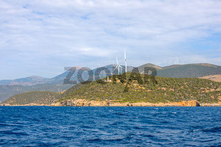 Lighthouse on a Hilly Shore and Wind Farms