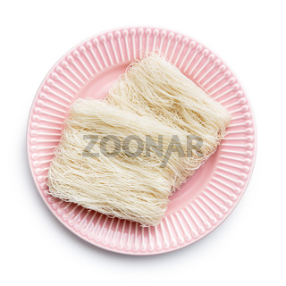 Uncooked white rice noodles on pink table.