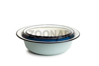 Old enamel dishes on white background
