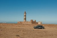 Old car and lonely tower in the desert