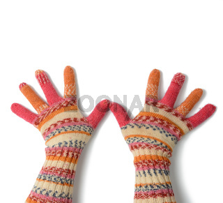 two female palms in knitted multi-colored mittens on a white background