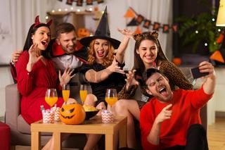 happy friends in halloween costumes taking selfie