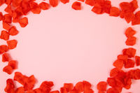 Frame of red rose leaves on pink background with copy space