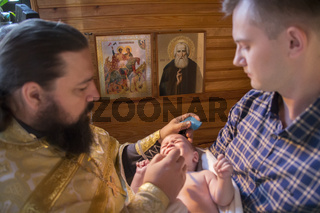 Belarus, Gomel, September 17, 2018. Prudkovsky church. The baptism of the child.Blurred priest and godfather hold the child on the background of icons
