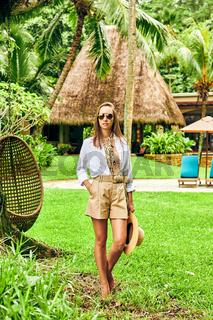 Woman on beach standing near resort bungalow