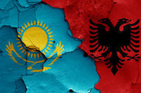 flags of Kazakhstan and Albania painted on cracked wall
