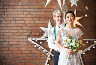 Cheerful married couple standing near the brick wall