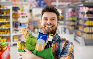 smiling young man with food in bag at supermarket