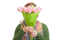 Elderly woman holding a bouquet of colorful tulips in front of her face, isolated on white background. Mothers day, Valentines day, Easter and surprise Concept.