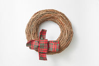 Handcraft round wreath from twigs on a white background.