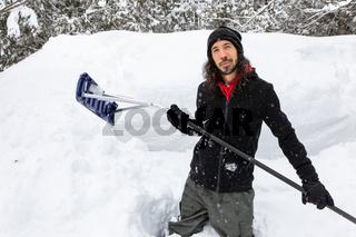 man standing between snow holding shovel