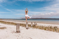 Beautiful woman balance on wooden post yoga pose in swimwear and sarong