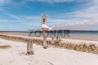 Beautiful woman balance on wooden post yoga pose in swimwear and sarong