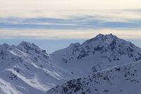Snowy slope in high mountains and sunlit cloudy sky at winter evening